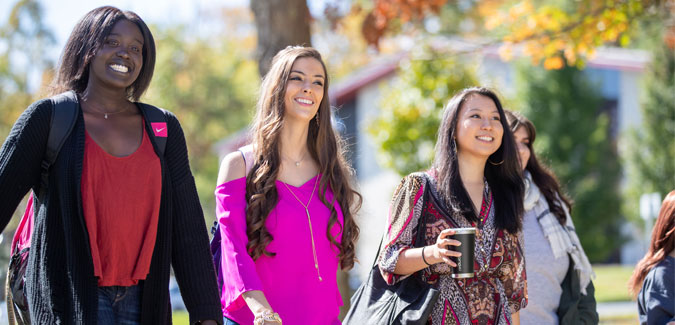 Students smiling and walking on campus