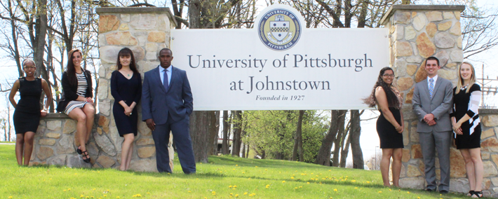 group of people standing next to Pitt Johnstown sign